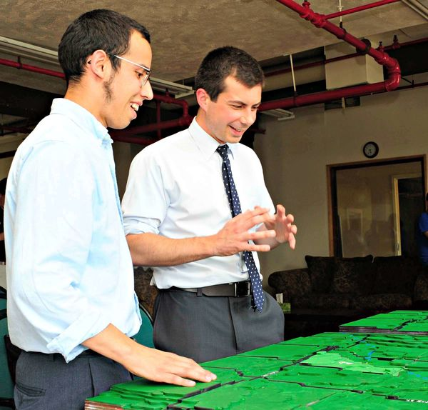 South Bend Mayor Pete Buttigieg and enFocus Fellow Jonathan Schommer look at a topographical map of Bowman Creek
